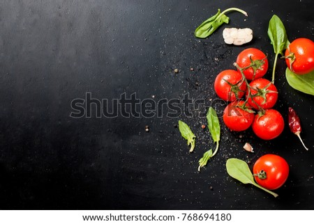 Branch ripe raw tomatoes, garlic and herbs on black background. Copy space.