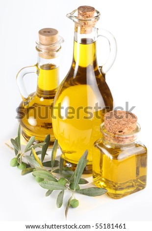 Branch with olives and a bottles of olive oil isolated on white