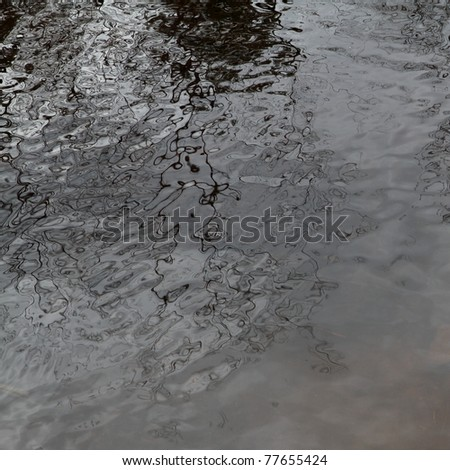 Branches and clouds reflected in a rippled pond surface