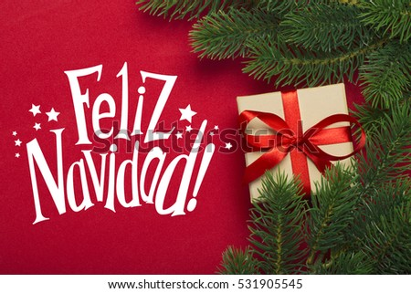 Branches of a Christmas tree and gift on a red background with the wishes of Merry Christmas in Spanish