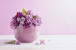 branches of blooming lilac in a cup on a purple background