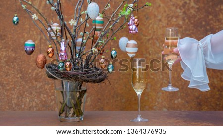 Branches with flowers and buds. Easter eggs and Easter bunnies hang on the branches. Womans hand give champagne glass. Festive clothes.