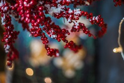 Branches with red berries covered with snow over blurred bokeh lights background , copy space, selective focus. Christmas background.