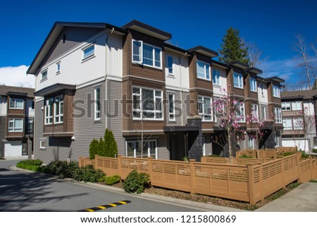 Brand new apartment building on sunny day in spring with blooming trees in British Columbia, Canada.