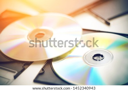 Brand new CDs with music lie on a white table among the black boxes for discs and shimmer with different bright colors from the sun.