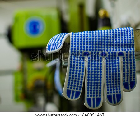 Brand new, clean, made from cotton with rubber dots on top, working glove, protective equipment for mechanic hands, safety at work, ready for work