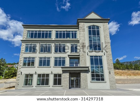 Brand new commercial building with retail and office space available for sale or lease.\ New office building with parking stalls in front and blue sky background awning opening.