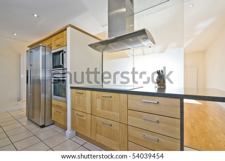 Brand new contemporary open plan kitchen with modern appliances and double American style fridge
