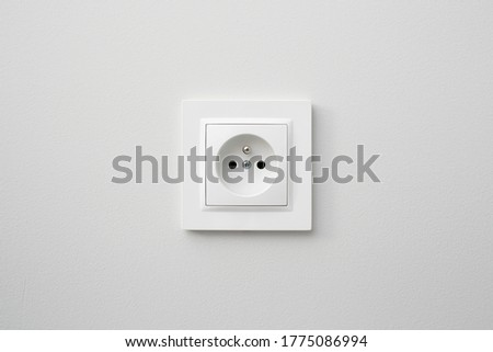Brand new electrical socket isolated on gray wall. Renovated studio apartment power supply background. Empty copy space white plastic power outlet. Photo stock ©