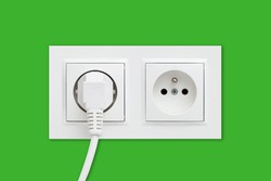 Brand new electrical socket isolated on green wall. White wire plug plugged in. Renovated studio apartment power supply background. Empty copy space double white plastic power outlet.