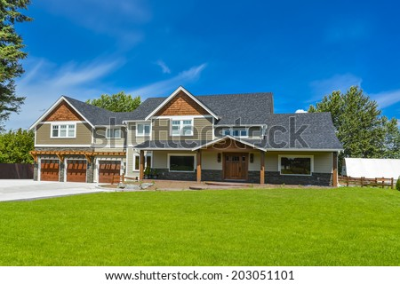 Brand new farmer\'s house in British Columbia, Canada. Huge family house with three garage door and blue sky background.