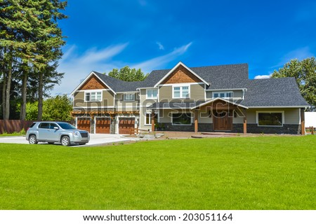 Brand new farmer\'s house with car parked on driveway in front. Huge family house with three garage door and blue sky background. British Columbia, Canada.