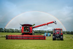 Brand new modern clean combine harvester and shiny red agricultural tractor in rural farm field on summers day with beautiful colourful rainbow in the sky behind