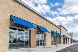 Brand new no logo, signage or label storefront of a under construction strip mall in the USA with blue awnings above the entrance, blue cloudy sky reflecting on the windows