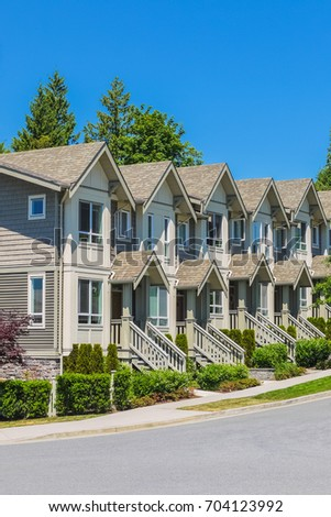 Brand new townhouses in a row on bright sunny day
