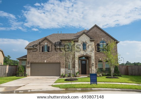 Brand new two story residential house in suburban American neighborhood at Humble, Texas, US. Newly constructed, freshly built modern home with landscaped yard. #693807148
