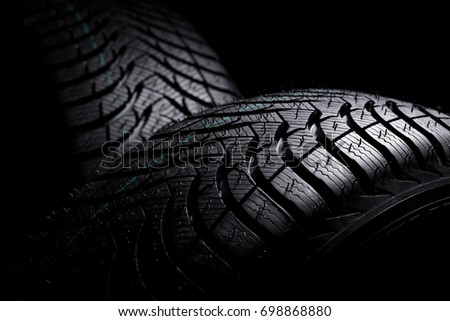 Brand new winter tires with a modern tread on the black background #698868880