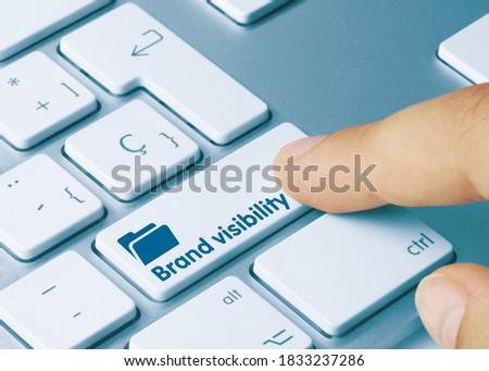 Brand visibility Written on Blue Key of Metallic Keyboard. Finger pressing key. Foto stock ©
