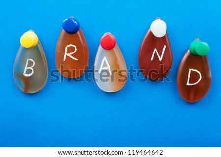 Brand word spelled with agates pinned on the board
