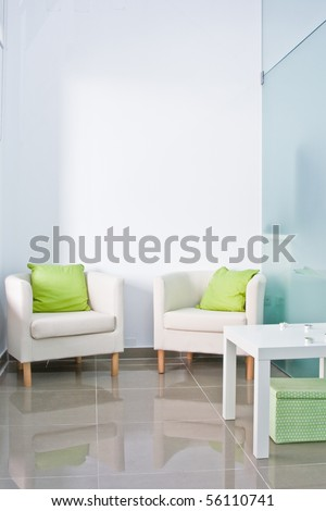 Brandable waiting room with two armchairs and white wall on the back.
