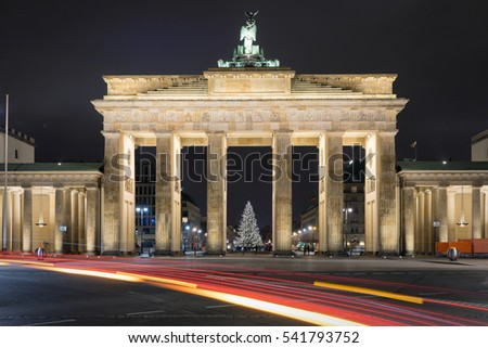 Brandenburg Gate in Berlin by night with Christmas tree and blurred traffic lights