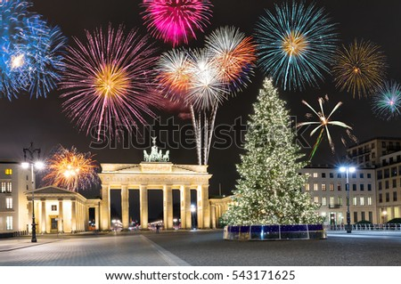 Brandenburg Gate in Berlin, Germany, with fireworks and Christmas tree
