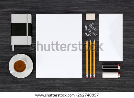 Branding identity mock up with templates for design presentation or portfolio on black table. Includes envelopes, paper, notebook, pencils, eraser, clips, lighter, cup of coffee.