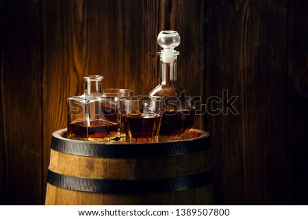 brandy and brandy in decanters stand on an oak barrel, strong alcoholic drinks in the basement #1389507800
