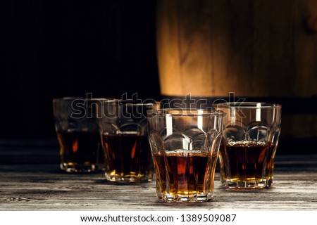 brandy and brandy in decanters stand on an oak barrel, strong alcoholic drinks in the basement #1389509087