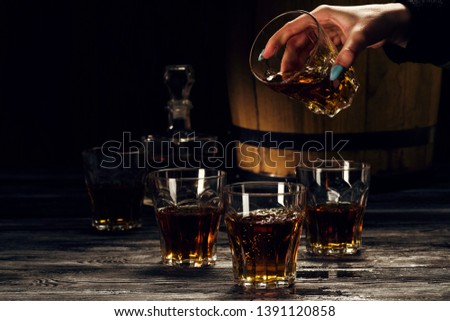 brandy and brandy in decanters stand on an oak barrel, strong alcoholic drinks in the basement #1391120858