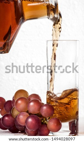 Brandy and grape. Brandy pours into a glass goblet, near which lies a bunch of grapes against a white foam #1494028097