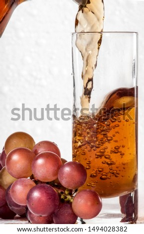 Brandy and grape. Brandy pours into a glass goblet, near which lies a bunch of grapes against a white foam #1494028382