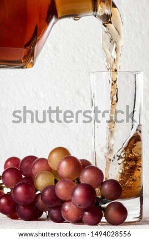 Brandy and grape. Brandy pours into a glass goblet, near which lies a bunch of grapes against a white foam #1494028556