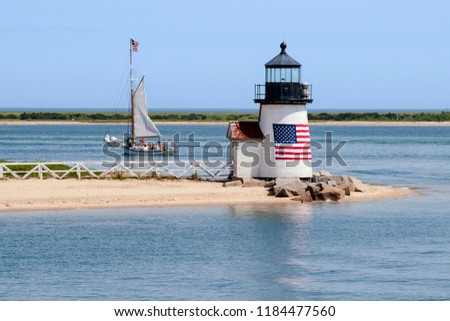 Brant Point lighthouse, with its American flag wrapped around its wooden tower, guides a sailboat out of Nantucket Island harbor in Massachusetts. #1184477560