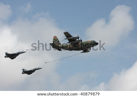 BRASILIA, BRAZIL - 7 SEPTEMBER: Refueling procedure of two Mirage F-2000 from a Hercules C-130, during an air show with the occasion of National Day of Brazil September 7, 2009 in Brasilia, Brazil