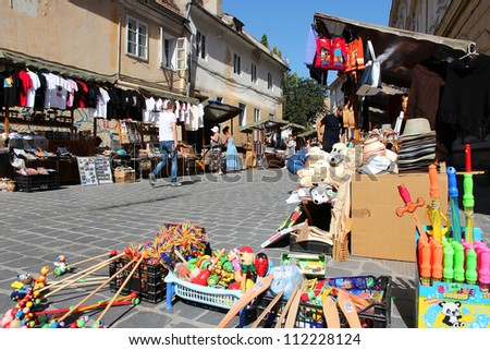 BRASOV, ROMANIA - AUGUST 21: Tourists shop at souvenir stalls on August 21, 2012 in Brasov, Romania. Brasov is a popular tourism destination with 581,983 arrivals in Brasov County in 2008.