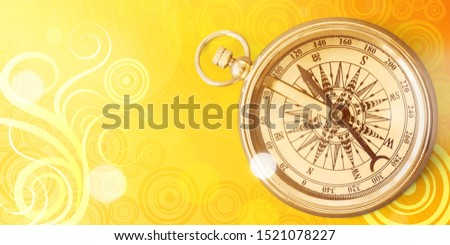 Brass antique compass on wooden background