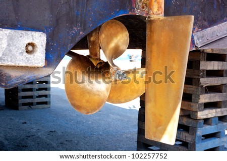 brass boat propeller and steering in beached ship