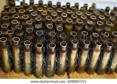 Brass cases of cartridges in a machine-gun tape #608885555