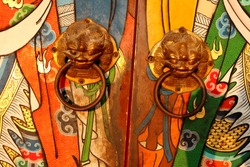 Brass door knobs are on bright colorful door and shape tiger head, the door knobs are design chinese style in shrine, Thailand.