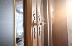 Brass door with glass inserts and handles with ornate escutcheons on a wooden cabinet , close up, authentic interior home