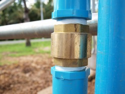 Brass fitting on PVC pipe. Installed beside blue PVC pipe on steel pipe background and blurred green tree. Focus close and choose the subject.