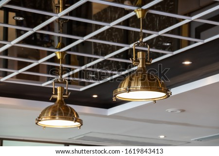 brass hanging lamps on mirror ceiling. golden pendant light decorate in dining room. metal lantern for interior light. stock photo
