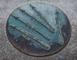 Brass mile marker with patina at Gettysburg, Pennsylvania, with distances shown to the Wheat Field, Devil's Den, Round Top, and Little Round Top.