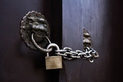 Brass padlock and chain on a ancient door