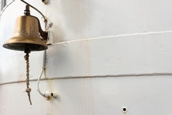 Brass ship's bell on the exterior of a fire fighter boat, white painted metal, copy space, horizontal aspect
