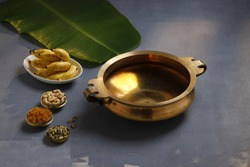 Brass vessel,south indian traditional metal vessel named urule ,which is arranged to make payasam or kheer using cashewnut,kismiss  and cardamom to garnish with grey background,selective focus