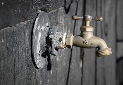 Brass water spigot on black wall.