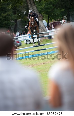 BRATISLAVA, SLOVAKIA - AUGUST 13: spectators watch as Andy Candin on horse Carlo 281 jumps over hurdle at Grand Prix Bratislava on August 13, 2011 in Bratislava, Slovakia