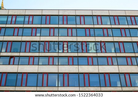 Bratislava, Slovakia - 4/19/2019: Detail photo of a business building with windows with red details during the day.
